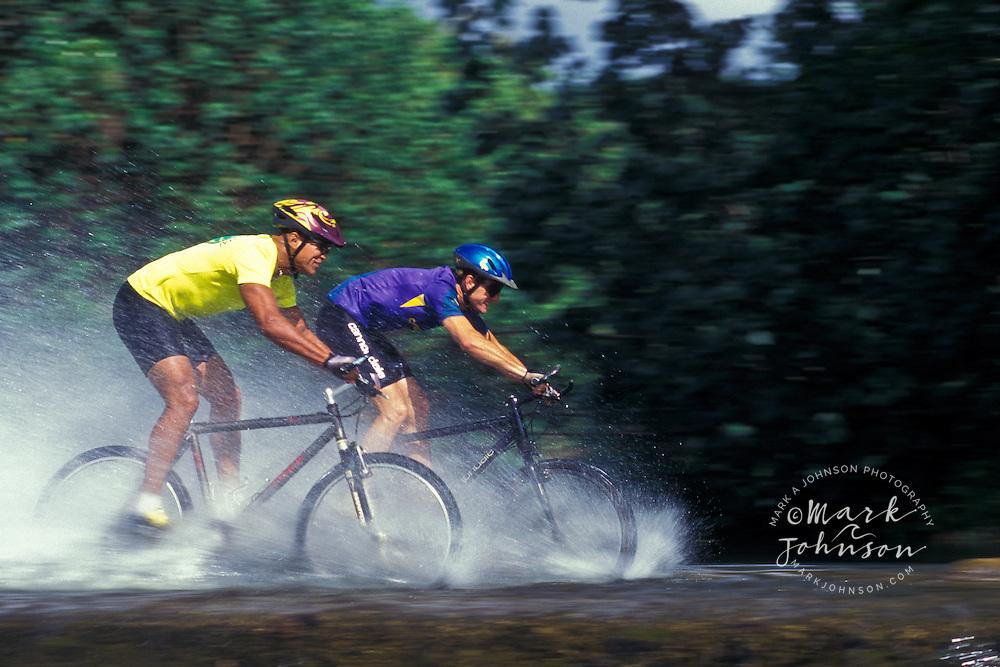 2 men mountain biking through stream, Kauai, Hawaii