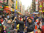 Teenagers blowing confetti in to the air during Chinese New year celebration Chinatown New York City