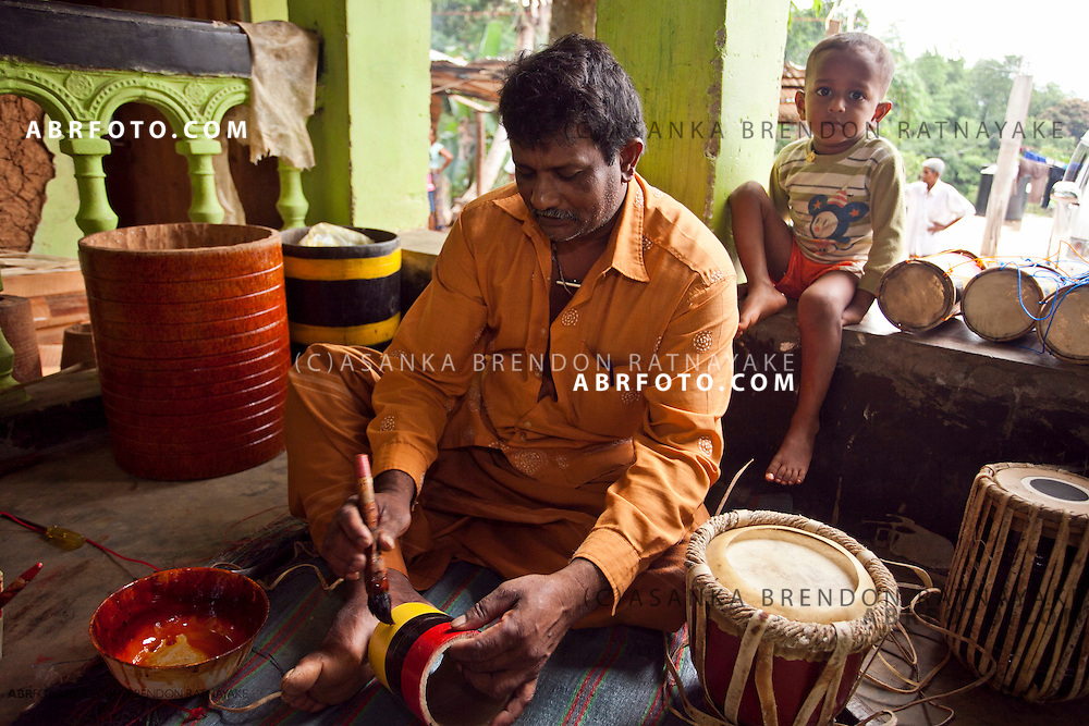 A drum craftsmen paints the barrel of a childrens toy drum as his son looks on.