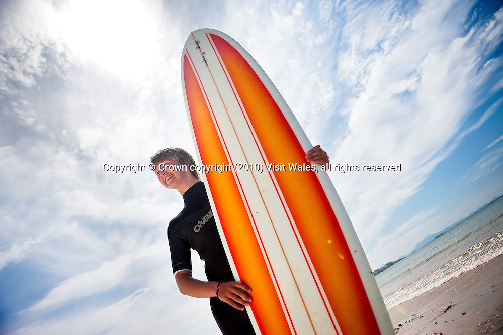 Young man holding surfboard on beach<br /> Surfing<br /> Rhosneigr<br /> Anglesey<br /> North<br /> Activities And Sports