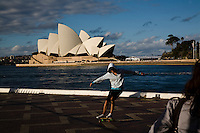 Sydney travel sites series.The Opera House from the water front of the overseas passager terminal in circular quay. A skate boarder one late winter afternoon.