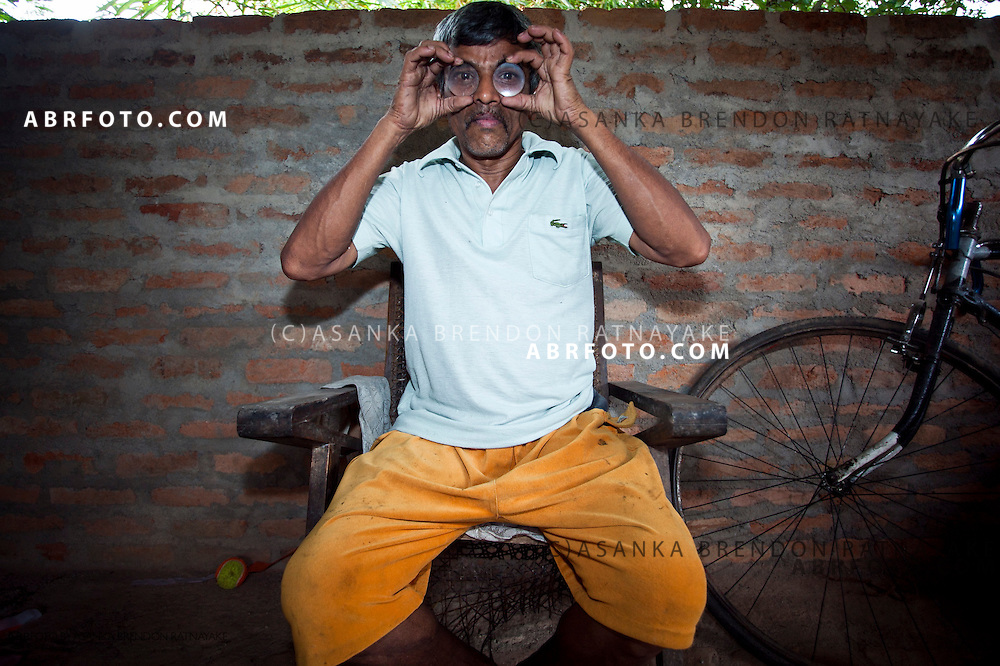 Mr Gunasoma, poses for a portrait holding up two different lenses he created by hand using rock crystal or Quartz.