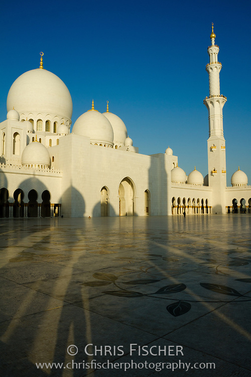 View of Sheikh Zayad Grand Mosque in Abu Dhabi from courtyard with morning shadows pointing towards the mosque.
