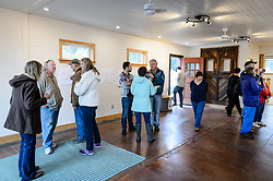 Joanne Waterman (second from left) greets visitors to the open house for the recently restored fire hall located on the grounds of historic Fort William H. Seward in Haines, Alaska.<br /> <br /> The fire hall was restored over a two-year period by owners Waterman and Phyllis Sage who also own the fort&rsquo;s original guardhouse, now a bed and breakfast, located next door to the fire hall.<br /> <br /> After being absent from the historic Fort Seward skyline since approximately the 1930s, the 60-foot tower of the fort&rsquo;s fire hall has been restored to its original height. The building and tower, built around 1904 in Haines, Alaska, was shortened to approximately half its height in the 1930s for unknown reasons. The restoration included rebuilding a missing 35-foot section of the 60-foot tower whose purpose was to dry fire hoses. The tower restoration was completed by building its four sections on the ground and then hoisting those sections with a crane into place on top of each other.<br /> <br /> Through the years, the historic Fort Seward area, a former U.S. Army post, has been referred to as Fort William H. Seward, Chilkoot Barracks, and Port Chilkoot. The National Historic Landmarks listing record for the fort says that &quot;Fort Seward was the last of 11 military posts established in Alaska during the territory's gold rushes between 1897 and 1904. Founded for the purpose of preserving law and order among the gold seekers, the fort also provided a U.S. military presence in Alaska during boundary disputes with Canada. The only active military post in Alaska between 1925 and 1940, the fort was closed at the end of World War II.&rdquo; <br /> <br /> The bottom portion of the fire hall is being leased as commercial space. Due to fire code restrictions there is no public access to the upper portion of the tower.