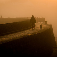 A man walks his dog on a foggy evening, Barry Island, Wales