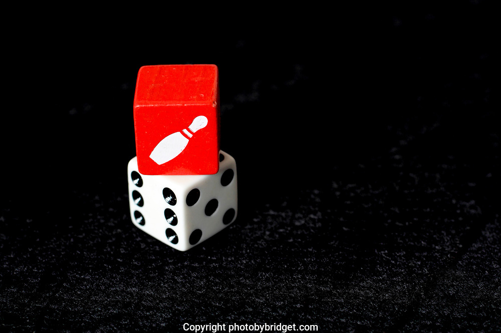 red and white dice. White with Numbers showing no. 6 the red on top of it showing a white nine-pin. Photographed on black backdrop