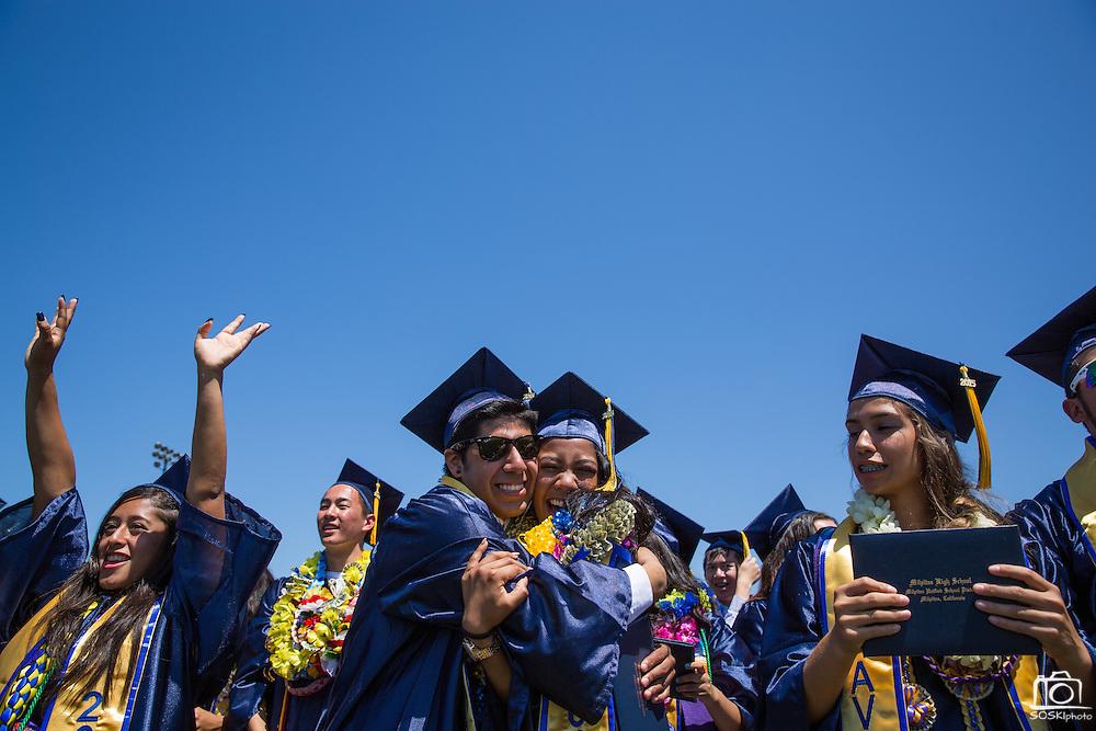 Geraldo Cruz, left, and Marhiel Antoinette Laya hug as classmates celebrate graduating after the graduation ceremony at Milpitas High School in Milpitas, California, on June 6, 2015. (Stan Olszewski/SOSKIphoto)