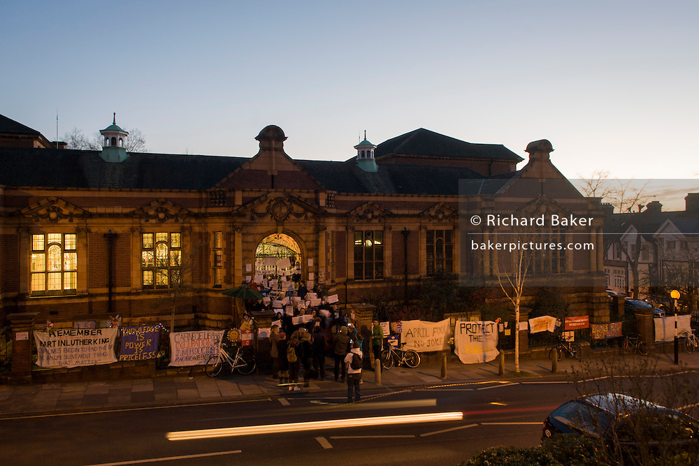An evening meeting by campaigners outside Carnegie Library in Herne Hill, south London while occupiers remain inside the premises day 7 of its occupation, 6th April 2016. The angry local community in the south London borough have occupied their important resource for learning and social hub for the weekend. After a long campaign by locals, Lambeth have gone ahead and closed the library's doors for the last time because they say, cuts to their budget mean millions must be saved.