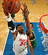 Florida's Marreese Speights (34) powers to the rim against the defense of Vermont's Marqus Blakely in the first half. Florida defeated Vermont 86-61.