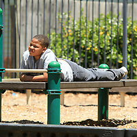 Ashtin Jefferson, 11, a student at Milam, takes a break on the playground equipment from playing football with his friends during the school's Field Day on Monday in Tupelo.