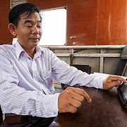 CAPTION: Mr Tam, from the Department of Natural Resources and the Environment, shows us data on salinity levels which is continuously uploaded to a website, in real time, and made available for anyone to access. LOCATION: Salinity Monitoring Station # 2, Can Tho, Vietnam. INDIVIDUAL(S) PHOTOGRAPHED: Doan Thanh Tam, DONRE and CEM Staff.