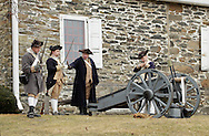 Newburgh, New York  - Revolutionary War reenactors in uniforms drill by a cannon at Washington's Headquarters State Historic Site as part of George Washington's birthday celebration on Feb. 18, 2012. The reenactors are from John Lamb's Artillery Company. Their cannon is modeled on the British three-pounder field piece. Hasbrouck House, the longest-serving headquarters of Washington during the American Revolution, is in the background.
