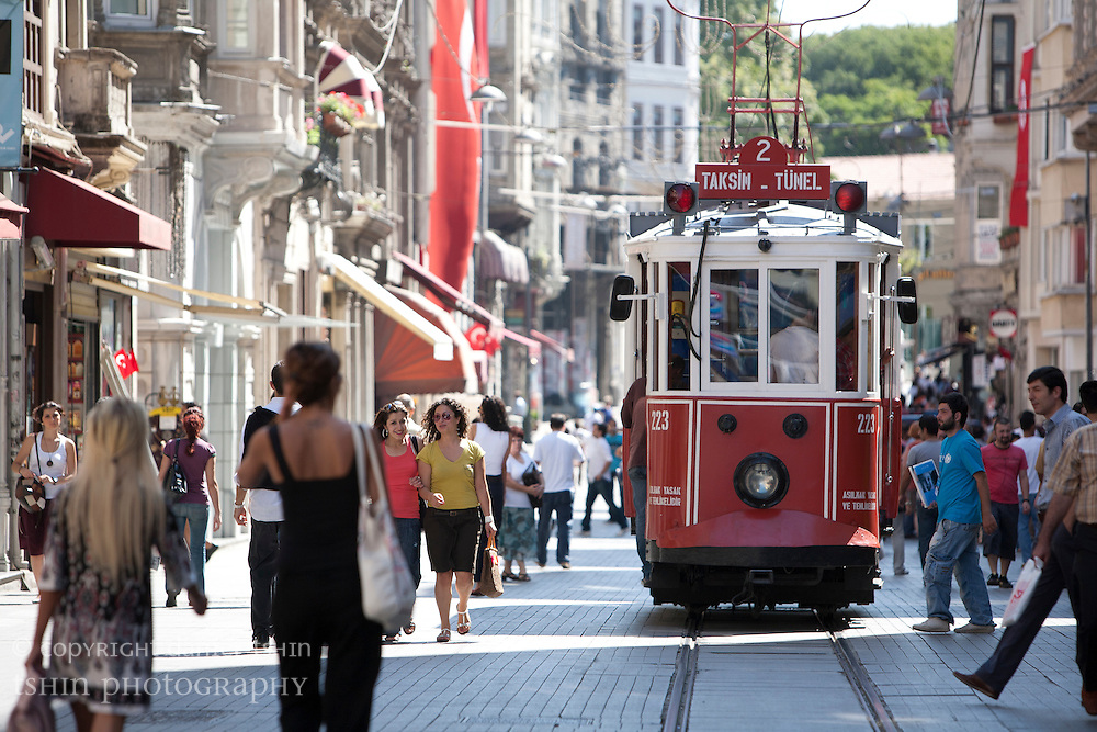 The historic tram traveling along ?stiklal Avenue full of pedestrians in Beyo?lu.