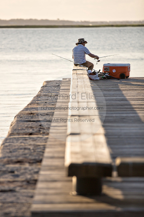 A man fishing along waterfront park in the historic district of Charleston, SC.