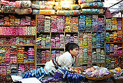 A store keeper at the busiest market in Thailand finds some time to make a phone call. The Chatuchak market also frequently called the J.J. market is the biggest weekend market in the world. It receives roughly 200,000 visitors each day.