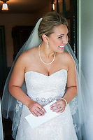 A bride holds a letter for the groom as she peeks out of the doorway at the West Overton Museum.