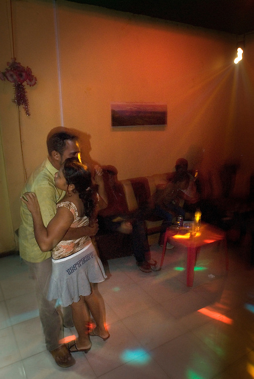 A young man dances with a girl in a Dili bar frequented by prostitutes.