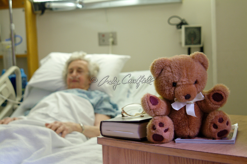 Mature woman resting in post operative recovery room at hospital with get well stuffed teddybear gift on table, USA.Released