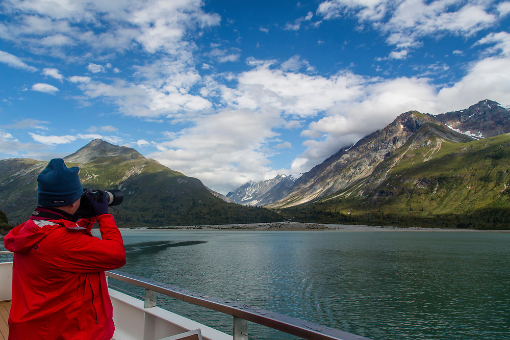 A photographer shoots from the stern of a tour boat at water, mountains and sky. Glacier Bay.
