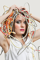 Portrait of young woman with head tangled in colorful cables over gray background