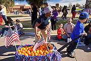 16 JANUARY 2012 - MESA, AZ: A woman gives out oranges during the parade on Martin Luther King Day in Mesa, AZ, Monday, Jan. 16. Hundreds of people participated in the parade which marched through downtown Mesa.    PHOTO BY JACK KURTZ