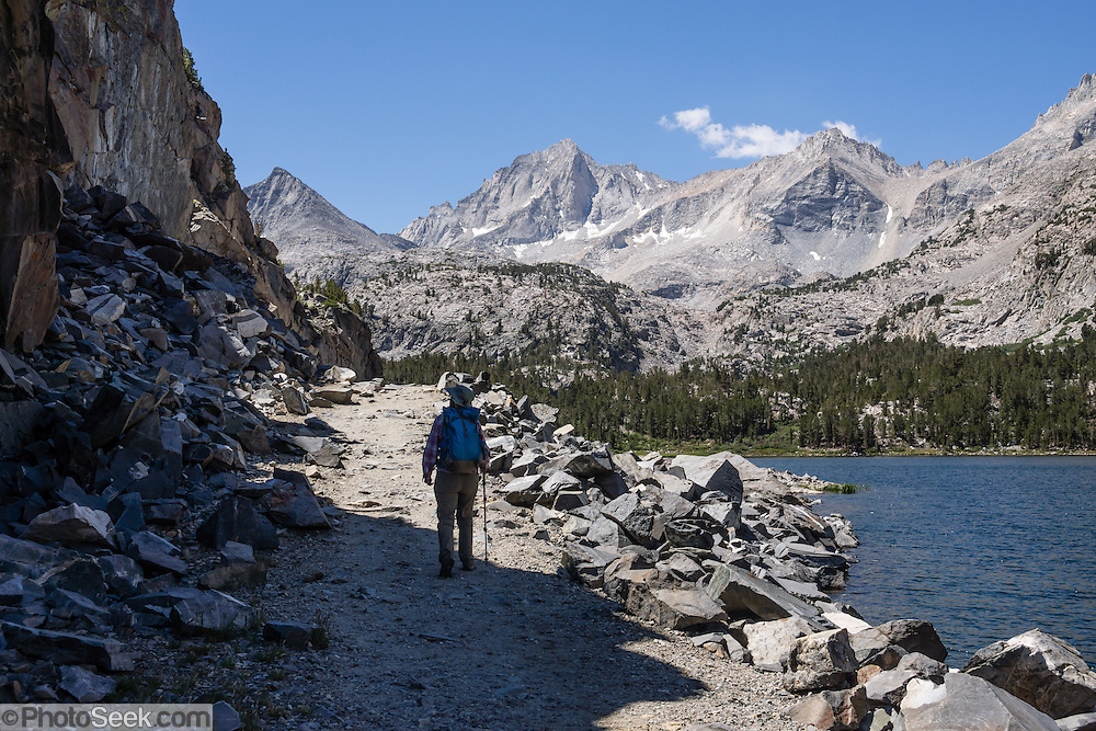 A hiker explores Long Lake in John Muir Wilderness, Little Lakes Valley, Inyo National Forest, Sierra Nevada, California, USA. Enjoy an easy, very rewarding hike from Mosquito Flat through Little Lakes Valley to Chickenfoot Lake and Gem Lakes. To reach the trailhead, turn off Highway 395 at Toms Place (15 miles south of Mammoth Junction) onto paved Rock Creek Road, and drive 10.5 miles to the end. We hiked the moderate trail to Morgan Pass, 7.5 miles round trip with 1250 feet cumulative gain; but you should skip the left turn to redundant Morgan Pass and instead turn right to visit the pretty Gem Lakes.
