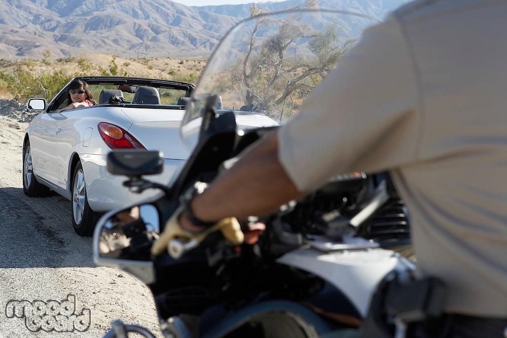 Police officer on motorbike stopping car on desert road side