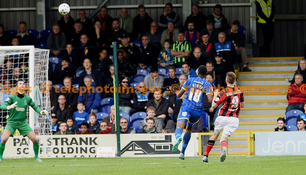 Tom Barkhuizen of Morecambe chips James Shea in the Wimbledon goal to score their fourth goal during the Sky Bet League 2 match between AFC Wimbledon and Morecambe at the Cherry Red Records Stadium in Kingston. October 17, 2015.<br /> Simon  Dack / Telephoto Images<br /> +44 7967 642437
