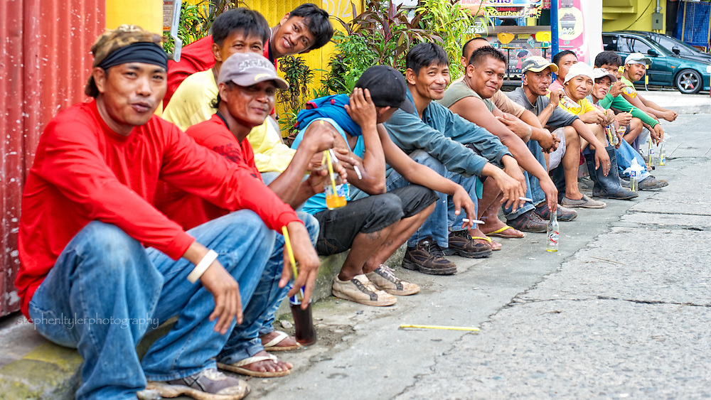 A group of hard working laborers taking a morning break on the curb.