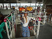 30 OCTOBER 2015 - YANGON, MYANMAR:  A snack vendor with his load precariously balanced on his head climbs the stairs on the Dala ferry. The ferry to Dala runs continuously through the day between Yangon and Dala. Yangon, Myanmar (Rangoon, Burma). Yangon, with a population of over five million, continues to be the country's largest city and the most important commercial center.          PHOTO BY JACK KURTZ