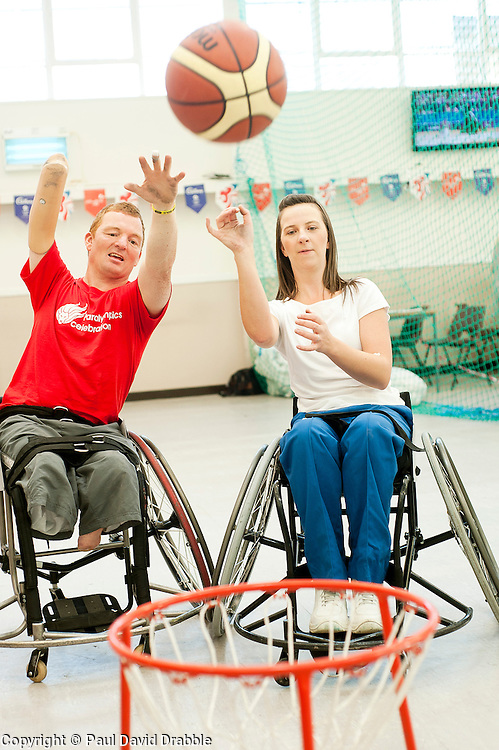 Cadbury 2012 Paralympic demonstration Sheffield..Kraft Lab scientist Kayleigh Jones tries her hand at wheelchair basketball alongside coach Andy Atkinson who was on site with the  RGK Rhinos Sporting club wheelchair basketball team to give Sheffield colleagues an insight into Wheelchair basketball, Paralympic sports and promote awareness around the different sporting disciplines.   .  ....3 September 2012.Image © Paul David Drabble