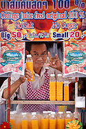A man selling fresh orange juice at Chatuchak JJ market in Bangkok, Thailand