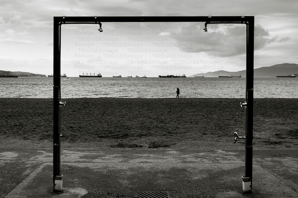 A lone silhouetted figured walking through a frame on a winters beach.