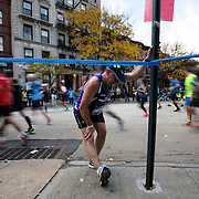 November 1, 2015 - New York, NY : A runner pauses alongside Marcus Garvey Park in Harlem to stretch as he competes in the 2015 TCS New York City marathon on Sunday. <br />  CREDIT: Karsten Moran for The New York TImes
