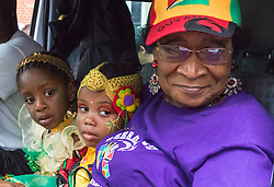 London, August 30th 2015. Tired children travel in the cab of a truck with their grandmother as revellers enjoy day one of the Notting Hill Carnival.