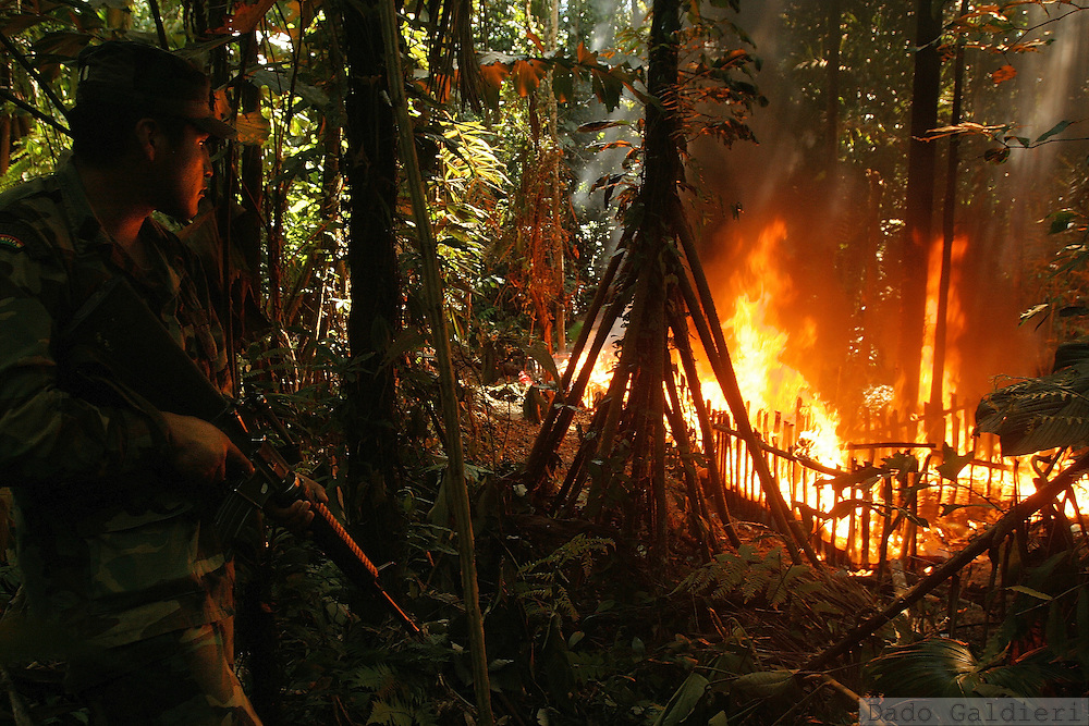 A Bolivian military officer looks on while a cocaine pit is burned in the middle of the rainforest region of Chapare in Bolivia on Tuesday, May 16, 2006.(Dado Galdieri)