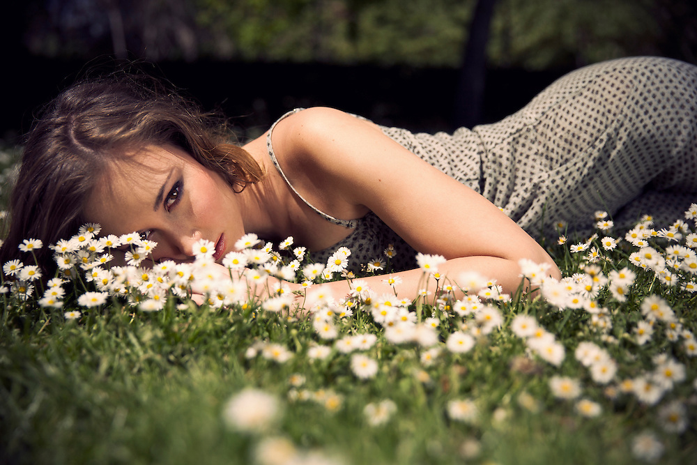 Young woman posing among daisies on a field in Madrid.