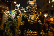 New York, NY, October 31, 2013. A woman in green and black is frozen by the flash while her skeletal partner is a bluur of motion in New York's Greenwich Village Halloween Parade.