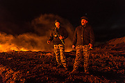 Police officers stand guard at one of the burning oil wells during the night.