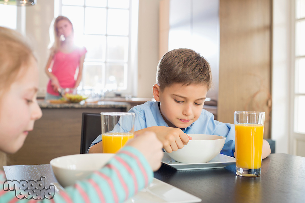 Siblings having breakfast at table with mother preparing food in background