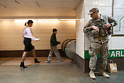 A member of the National Guard watches travelers walk past in the Arlington MBTA station in Boston, MA on Wednesday, April 17, 2013. Heightened security is still in effect around the city in the wake of the Boston marathon bombings on Monday.  (Matthew Cavanaugh for The Washington Post)