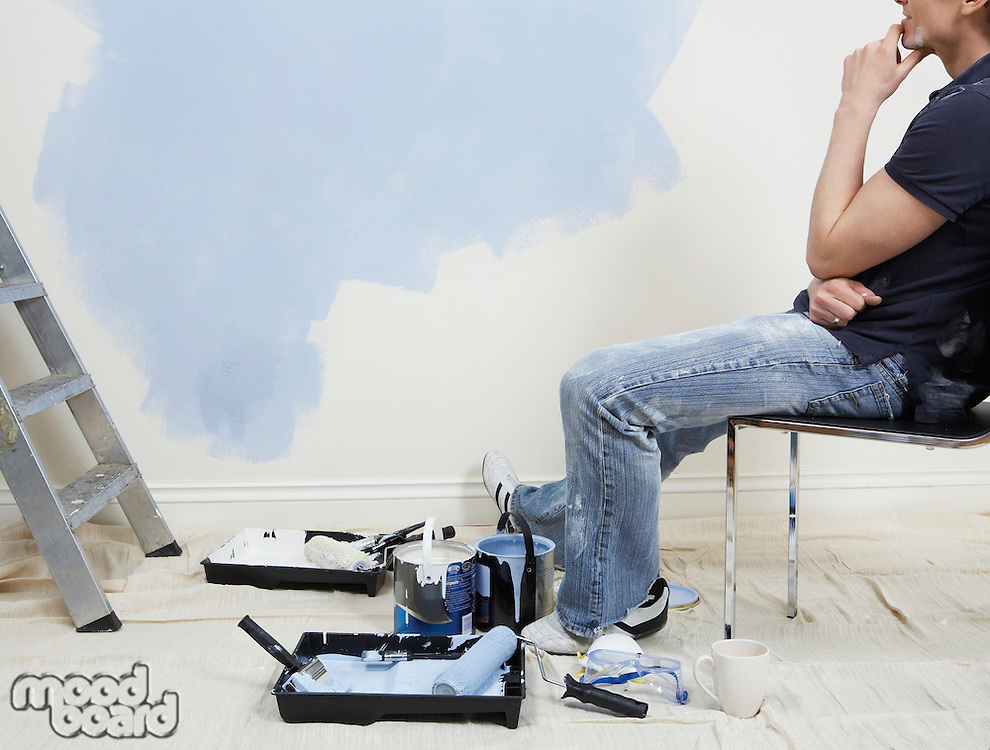 Man resting while painting wall low section