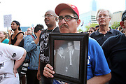 A protester holds a portrait of Marthin Luther King, Jr. and Malcolm X during an Anti Racism Rally at Dallas City hall on Saturday August 19, 2017.