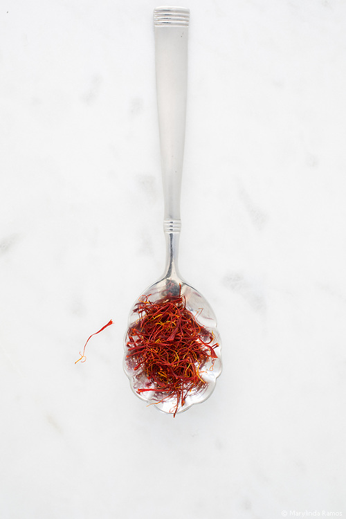 Saffron threads on a scalloped spoon on white marble.