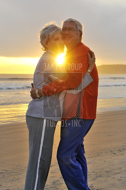 Senior couple hugging on the beach with a sunburst between them