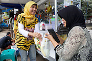 Nur Khayati, 24, serving a fruit smoothie to a customer.<br /> <br /> Nur was working in a restaurant when she downloaded the Usaha Wanita app. She wasn't planning to go into business then but the stories and advice about the need for women to be independent inspired her so much that she decided to invest her savings in setting up a juice stall.<br /> <br /> Her fruit is purchased daily and the juices are freshly prepared in front of the customer. <br /> <br /> Her business is just four months old but is already thriving. She has been able to give her parents 6 million rupiah, which they are investing in land to increase the size of their fruit farm. <br /> <br /> She is also opening a new booth in another part of town in two weeks time.