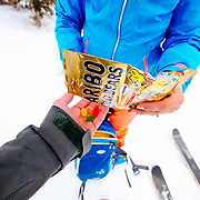 Jess McMillan hands over some gummi bears to photographer Jay Goodrich while exploring the backcountry near JHMR.