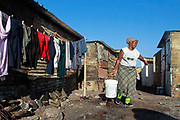 A South African woman carries water after washing clothes outside her shack  in Masiphumelele, an informal shack settlement in Cape Town, South Africa, on 16 May 2011. Housing and service delivery to poor areas are the major issues facing the ruling African National Congress (ANC) and its opposition parties as South Africans head to the polls 18 May 2011 to cast their ballots in the local government elections.  The ANC is expected to loose ground on oppostion parties in these elections seen as a barometer to the changing political landscape in Africas most successful democracy.