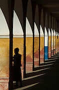 Southern Africa. Mozambique. Ilha de Mocambique. Stone Town. Silhouette of child in sun lite archway..DVD0013