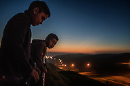 Young boys from the Arias family peer over the first, older US-built border wall at dusk into the flood-lit no-man's land created between the two walls/fences where US Border Patrol is present 24 hours a day, seven days a week.  Colonia Libertad, Tijuana, Mexico.  The Arias family is led by Estel, these boys&rsquo; grandmother and matriarch of the clan.  Their house actually rests up against the border wall and yet the family expressed no fear from human or drug traffickers.  Still their home, despite being millimeters from the world&rsquo;s superpower, lacks running water, necessitates an outhouse and they&rsquo;ve had to illegally tap into the power grid because they cannot afford to pay for electricity.  <br /> <br /> I happened upon their home on a previous reporting trip, one month ago, and was struck by strength of this family living in extreme poverty, through tutelage of the family matriarch.  The family not only worries what a new, bigger wall might mean but also they spoke about a plan to build a highway connecting the airport to their east with the main port of entry at San Ysidro, to the west right next to this wall.